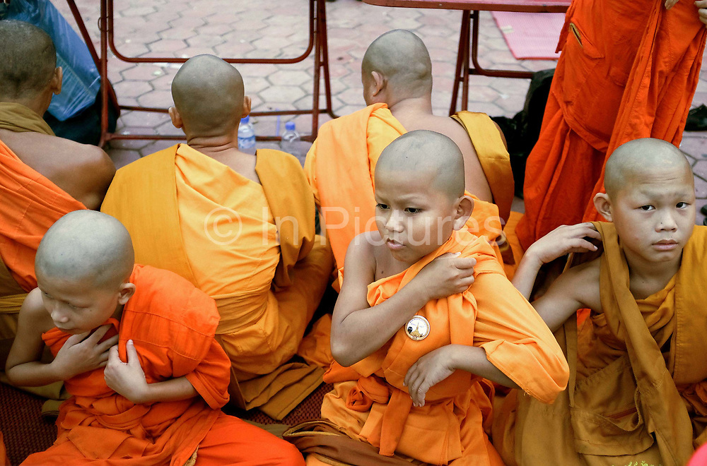 """Young novice monks at the That Luang festival, Vientiane, Lao PDR. Pha That Luang is the national symbol and most important religious monument of Laos. Vientiane's most important Theravada Buddhist festival, """"Boun That Luang"""", is held here for three days during the full moon of the twelfth lunar month (November). Monks and laypeople from all over Laos congregate to celebrate the occasion with three days of religious ceremony followed by a week of festivities, day and night. The procession of laypeople begins at Wat Si Muang in the city centre and proceeds to Pha That Luang to make offerings to the monks in order to accumulate merit for rebirth into a better life. The religious part concludes as laypeople, carrying incense and candles as offerings, circumambulate Pha That Luang three times in honor of Buddha."""