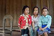 Three girl pose for a photo in the village of Naten which lies alongside the Lao/China border in Phongsali Province, Laos.