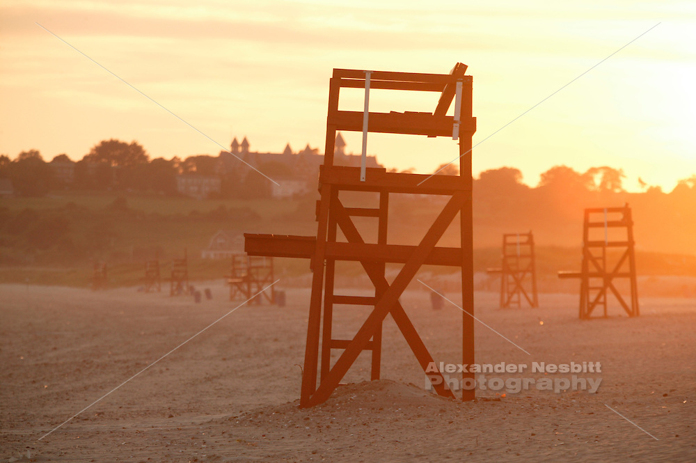 USA, Newport, RI - Hazy filled sunset on second beach with one lifeguard chair close backed by many more.