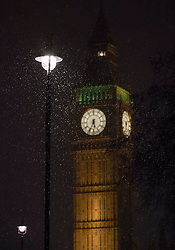 © Licensed to London News Pictures. 12/01/2017. London, UK. Snow flurries are illuminated by streetlight in Parliament Square in sight of Big Ben. Rain and heavy snow are expected to hit most of the UK today. Photo credit: Peter Macdiarmid/LNP
