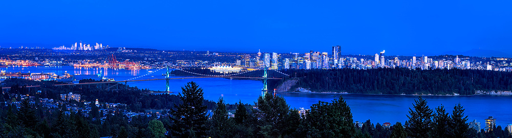 Blue Hour, Vancouver: This panoramic landscape captures an evening's blue cast, over Stanley Park and a distant downtown skyline, Vancouver British Columbia Canada.