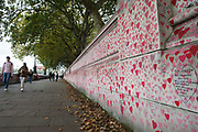 Members of the public walk alongside the National Covid Memorial Wall on the South Bank of the River Thames on 15th October 2021 in London, United Kingdom. The National Covid Memorial Wall is a public mural comprising thousands of red and pink hearts painted by volunteers in order to commemorate the victims of the COVID-19 pandemic in the United Kingdom.