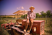 An Italian farmer sits on his tractor, taking a break from a day of hard work