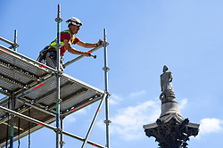 © Licensed to London News Pictures. 29/07/2020. LONDON, UK.  Nelson's Column is seen behind a construction worker removing scaffolding around artist Heather Phillipson's 'THE END', which will soon be unveiled to the public as the new Fourth Plinth artwork in Trafalgar Square.  THE END will show a giant swirl of replica whipped cream topped with a cherry, a fly and a drone.  Its drone will transmit a live feed of the square which can be watched on a dedicated website.  The installation, originally planned for 26 March 2020, but postponed due to the coronavirus pandemic will remain on display for the next year two years.  Photo credit: Stephen Chung/LNP