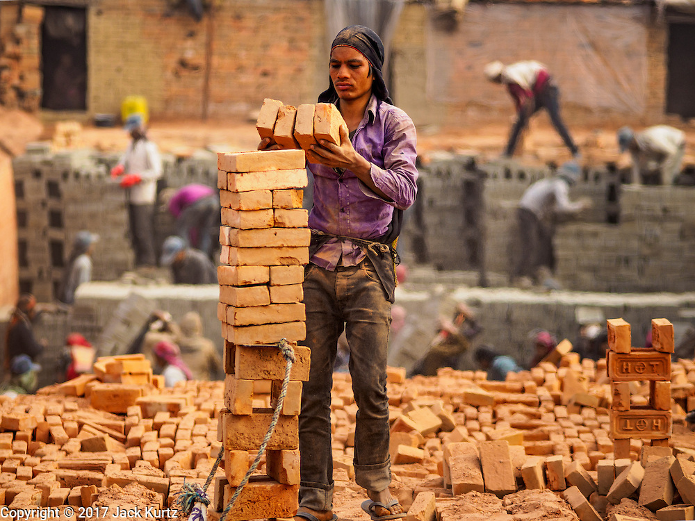 03 MARCH 2017 - BAGMATI, NEPAL: A worker stacks baked and finished bricks to a waiting truck while other workers, in the background, stack wet, unbaked, bricks in the kiln at a brick factory in Bagmati, near Bhaktapur. The wet bricks are gray in color. They turn their characteristic red after they are baked in the kiln. There are almost 50 brick factories in the valley near Bagmati. The brick makers are very busy making bricks for the reconstruction of Kathmandu, Bhaktapur and other cities in the Kathmandu valley that were badly damaged by the 2015 Nepal Earthquake. The brick factories have been in the Bagmati area for centuries because the local clay is a popular raw material for the bricks. Most of the workers in the brick factories are migrant workers from southern Nepal.       PHOTO BY JACK KURTZ