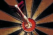 Dart in bulls eye of a dart board.