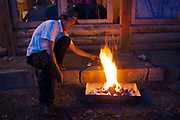 Man burning coals in preperation for a barbeque at Lugu Lake, Yunnan, China.