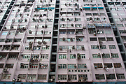 Busy apartment building in Wan Chai area of Hong Kong, China. Apartment blocks where people live stacked on top of each other in small rooms, with the exteriors covered in air conditioning units are all over the city. Dripping their condensed water onto people passing below.