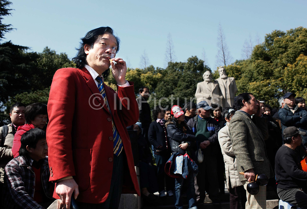 A man smokes a cigarette while watching a dancing show , near the Marx and Engles statue at  Fuxin Park in downtown Shanghai, China on 15 March, 2009. The park is popular place for pensioners.