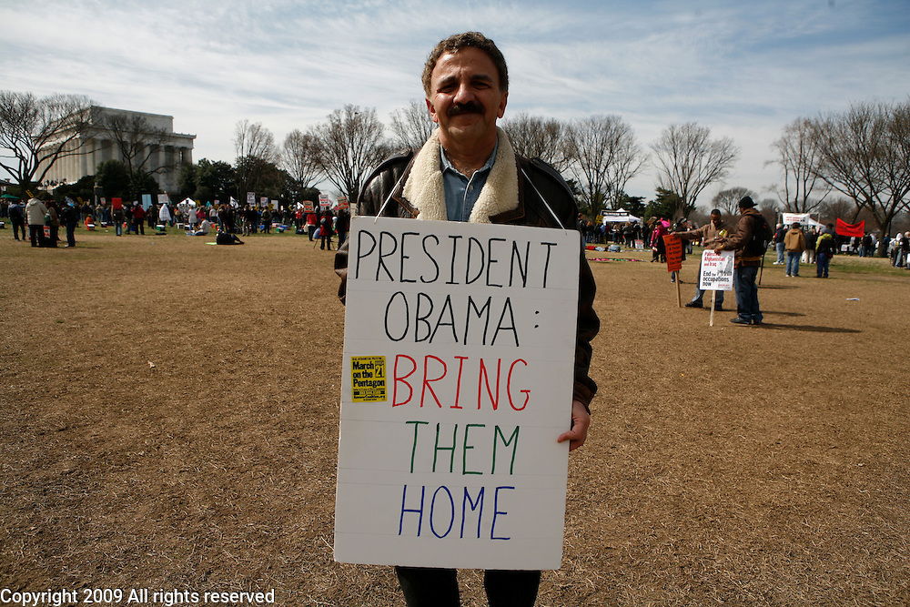 An anti war protester holds a sign with a message to Barack Obama before a protest against the war in Iraq.  March 21, 2009. Washington, D.C.