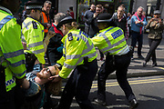 With his head supported, a protester is arrested by Met police officers at Oxford Circus on day 4 of protests by climate change environmental activists with pressure group Extinction Rebellion, on18th April 2019, in London, England.