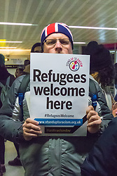 "St Pancras, London, January 16th 2016. Dozens of protesters hold an ""emergency demonstration and die-in"" as France prepares to bulldoze the Jungle Camp at Calais. PICTURED: A protester with his Stand Up To Racism placard and a Union Jack beanie.///FOR LICENCING CONTACT: paul@pauldaveycreative.co.uk TEL:+44 (0) 7966 016 296 or +44 (0) 20 8969 6875. ©2016 Paul R Davey. All rights reserved."