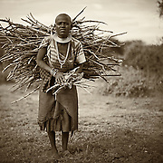 """""""Primative Life""""                                              Tanzania<br />  She carries the wood for cooking and warmth on her back, a hard life, a primitive life. Yet there is a look of contentment in their eyes. Knowing her family will be fed and the night will be warmed by the heavy load she carries."""