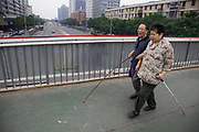 A blind couple walking arm in arm together in Fuchengmen, Beijing, China. Both using sticks to walk with they have formed an incredible partnership where one helps the other and that working as a pair in a team they can find their way around better. They were both walking with great confidence.