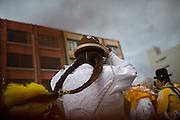"""María Eugenia Mamani Herrera, """"Claudina La Maldita"""", baila durante el carnaval en El Alto, Bolivia, el 18 de Febrero de 2012.<br /> <br /> En la ciudad de El Alto - ciudad vecina con La Paz, Bolivia- situada a una altura de 4,000 msnm, turistas y gente local hacen fila para comprar boletos para presenciar el espectáculo de las cholitas luchadoras.  Cada domingo un grupo de mujeres, las """"cholitas"""", se prepara para dar un espectáculo de lucha libre. Ellas portan la ropa tradicional de las mujeres Aymaras, que se ha mantenido desde la época colonial. Su atuendo consiste en faldas amplias, bombines -sombrero típico-, zapatos de plástico, trenzas hasta la cintura, joyas de gran tamaño, maquillaje y chales bordados.<br /> Yenny Wilma Maraz, conocida como """"Marta La Alteña"""", saluda al público con los brazos extendidos bailando al ritmo de la música, entrega su chal y su sombrero para subir al ring. Sube orgullosa aún siendo abucheada por el público. Ella es ruda y tendrá que pelear contra los buenos.<br /> La lucha libre es un espectáculo teatral, pero también requiere de un enorme esfuerzo físico y de entrenamiento constante para poder realizar vuelos desde las cuerdas del ring y soportar las caídas, que muchas veces son dolorosas.<br /> Los eventos de lucha libre son un negocio cada vez mayor. Cientos de turistas y bolivianos, asisten cada semana para ver a las cholitas vencer a sus adversarios. Las cholitas como otros luchadores pertenecen a grupos manejados por diferentes mánager, quienes en muchas ocasiones sacan ventaja, llevándose gran parte de las ganancias y dejando a ellas con casi nada. Esto ha creado divisiones, y por lo tanto, se han conformado nuevos grupos tales como Las Diosas del Ring, quienes ofrecen su espectáculo en diferentes puntos de la ciudad. La lucha libre boliviana ha ganado popularidad y ha traspasado fronteras gracias a las Cholitas luchadoras."""