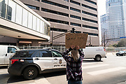 A demonstrator holds a sign in support of George Floyd around the Hennepin County Government Center, the site of the trial of former Minneapolis Police officer Derek Chauvin in Minneapolis, Minnesota, on Tuesday, March 9, 2021.