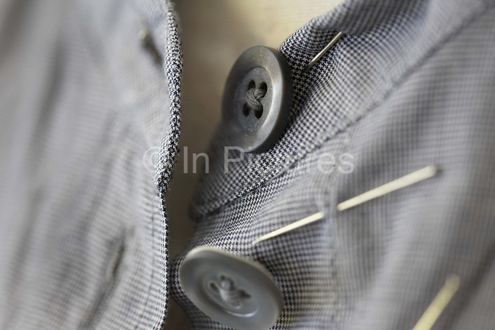 "A detail showing the fine stitching of a cotton dress by couturier Margaret Howell in the company's workshop factory in Edmonton, North London. England. In close-up, the eye is drawn into the centre of focus where the buttons are held in a criss-cross stich in its four holes. There are pins in this still prototype design as it evolves from an idea on paper to an actual garment. The fine check pattern of its fabric is beautifully sewn together in this fine and intricate dress. Howell is one of Britain's more understated of couture brands alongside more flamboyant personalities. Howell admits to being ""inspired by the methods by which something is made .. enjoying the tactile quality of natural fabrics such as tweeds, linen and cotton in a relaxed, natural and lived in look."""