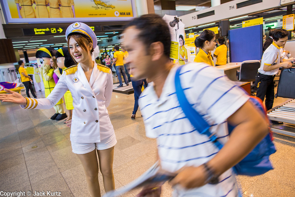 01 OCTOBER 2012 - BANGKOK, THAILAND:  A Nok Air spokesmodel greets passengers at the Nok Air counters during the grand reopening on Don Mueang International Airport in Bangkok Monday. Don Mueang International Airport is the smaller of two international airports serving Bangkok, Thailand. Suvarnabhumi Airport, opened in 2006 is the main one. Don Mueang was officially opened as a Royal Thai Air Force base on 27 March 1914 and commercial flights began in 1924. Don Mueang Airport closed in 2006 following the opening of Bangkok's new Suvarnabhumi Airport, and reopened as a domestic terminal for low cost airlines after renovation on 24 March 2007. Closed during the flooding in 2011, Don Mueang was again renovated and reopened in 2012 as the airport for low cost airlines serving both domestic and international passengers. On Monday, Air Asia, Asia's leading low cost airline, transferred all of their flight operations to Don Mueang and the airport was officially reopened. Suvarnabhumi International Airport is already over capacity and Don Mueang's importance as a hub is expected to grow.   PHOTO BY JACK KURTZ
