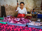11 OCTOBER 2016 - UBUD, BALI, INDONESIA:  A vendor cuts meat in the morning market in Ubud. The morning market in Ubud is for produce and meat and serves local people from about 4:30 AM until about 7:30 AM. As the morning progresses the local vendors pack up and leave and vendors selling tourist curios move in. By about 8:30 AM the market is mostly a tourist market selling curios to tourists. Ubud is Bali's art and cultural center.     PHOTO BY JACK KURTZ