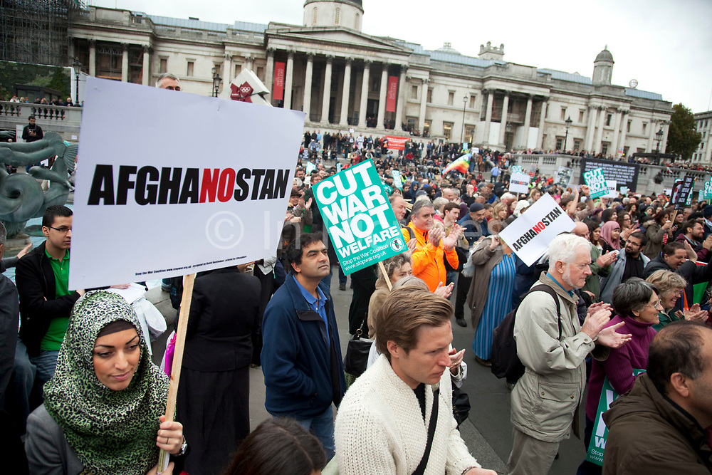 """Muslim woman with an Afghanostan placard and the crowd in Trafalgar Square. Protest in central London to mark 10 years of the conflict in Afghanistan. Musicians, actors, film-makers and MPs are joining protesters for the Anti-war Mass Assembly in Trafalgar Square. The Stop The War Coalition said up to 5,000 people were at the protest but a BBC correspondent estimated there were about 1,000 people in the square. The coalition says opinion polls show most British people want a """"speedy withdrawal"""" of UK forces. The demo brought together people from many groups in solidarity."""