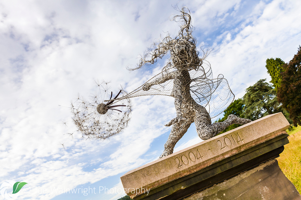 A life sized fairy, called 'Wishes' stands on a plinth beside the lake at Trentham Gardens, Staffordshire. it commemorates the first ten years of the garden's regeneration. The artwork was created by Robin Wight from galvanised and stainless steel wire