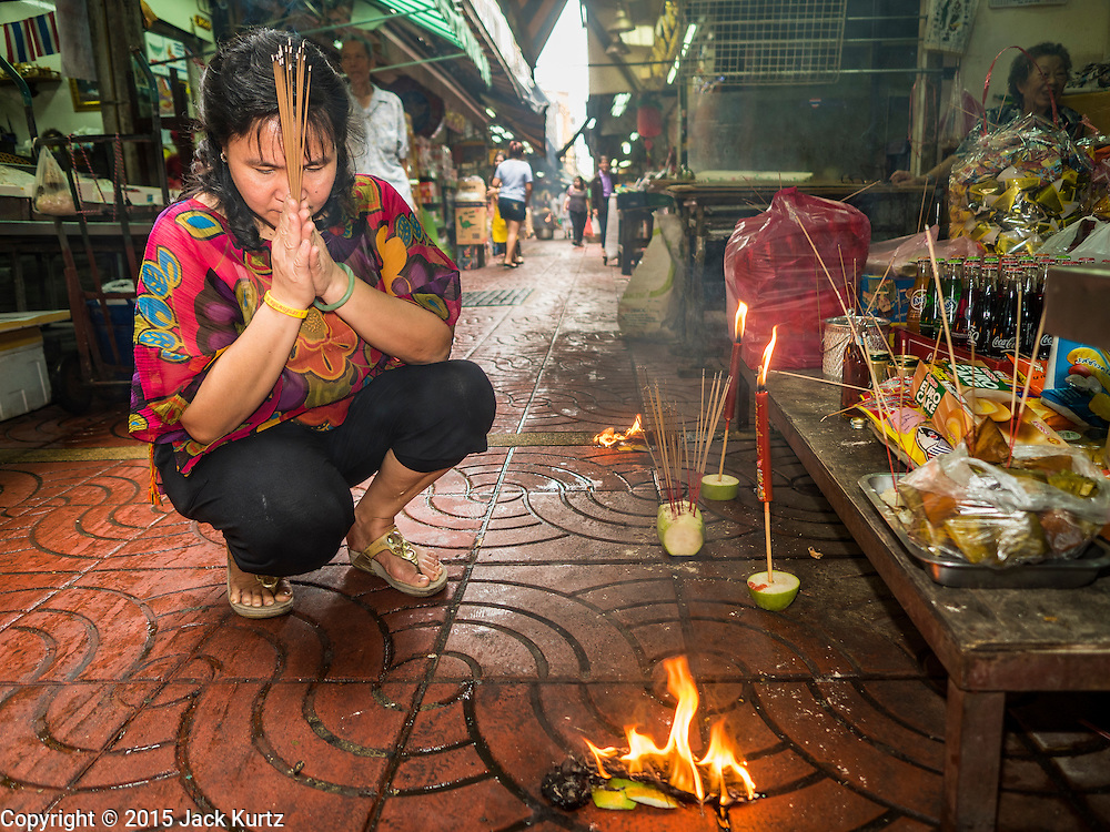 "28 AUGUST 2015 - BANGKOK, THAILAND: A woman prays and burns ""ghost money"" for her ancestors on Hungry Ghost Day in Bangkok's Chinatown. Mahayana  Buddhists believe that the gates of hell are opened on the full moon of the seventh lunar month of the Chinese calendar, and the spirits of hungry ghosts allowed to roam the earth. These ghosts need food and merit to find their way back to their own. People help by offering food, paper money, candles and flowers, making merit of their own in the process. Hungry Ghost Day is observed in communities with a large ethnic Chinese population, like Bangkok's Chinatown.        PHOTO BY JACK KURTZ"