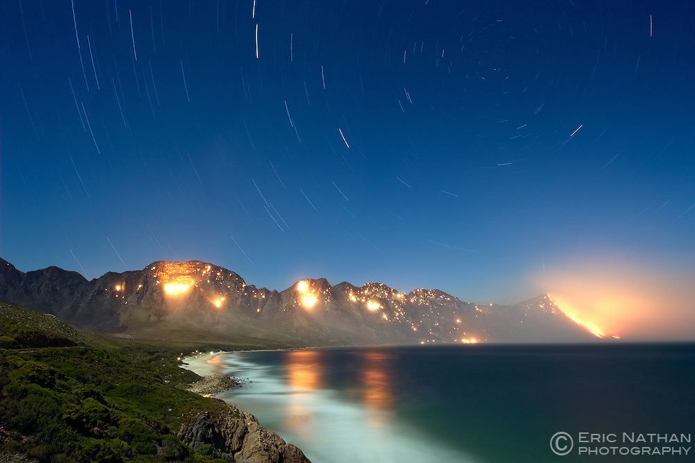 Night-time, moonlit view of a wild fire in the Kogel Bay Nature Reserve near Koeël Bay in False Bay, Western Cape, South Africa.