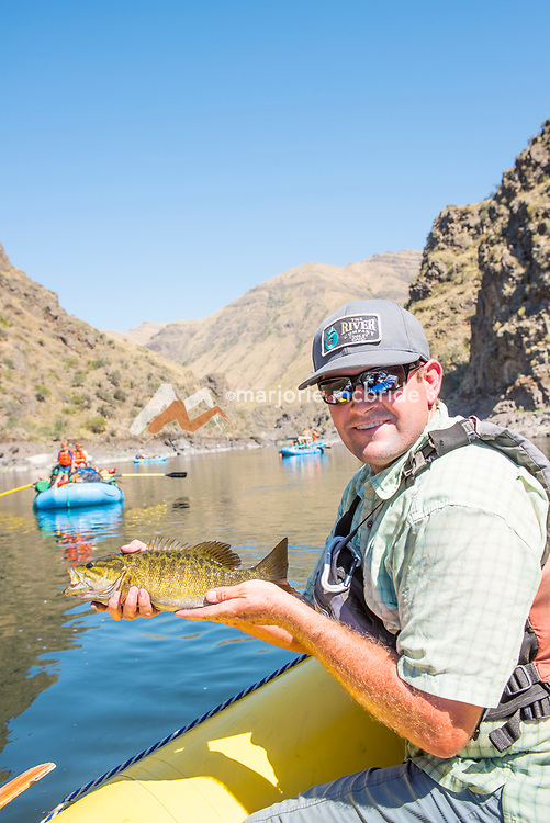 Man holding catch and smiling while fishing for Small Mouth Bass during a rafting trip on the Main Lower Salmon River, Hammer Creek to Hellar Bar, Idaho.