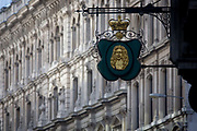 A detail of a City of London Goldsmith's ornate street sign on the corner of Suffolk Lane and Lombard Street in the heart of the capital's financial district. A golden crown sits above the head of an eminent 18th century financier. Such hanging signs were banned by Charles II, but replicas were erected for the coronation of Edward VII in 1902.