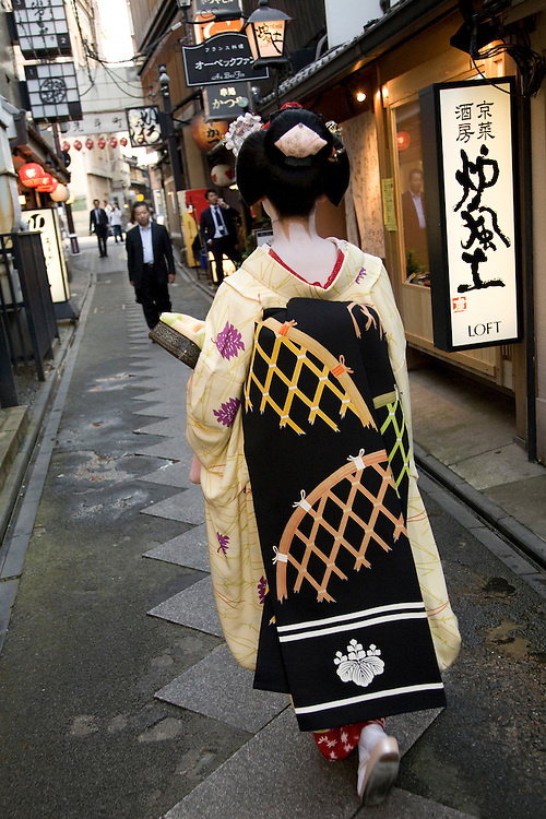 Asia, Japan, Honshu island, Kyoto, Geisha in kimono walking by restaurants on Pontocho, a pedestrian-only street in Gion district