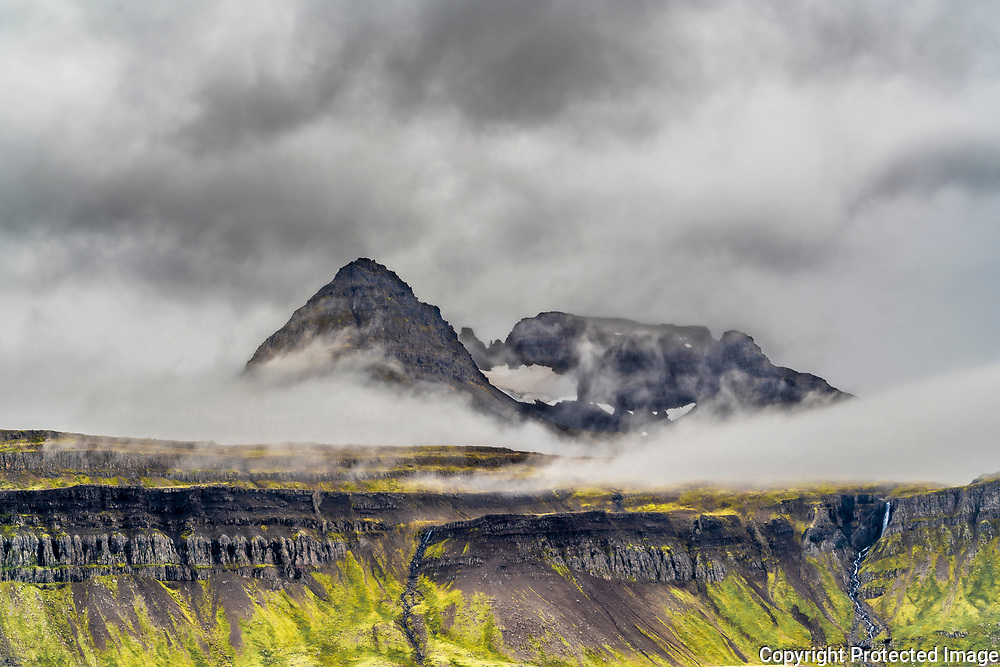 The peaks along Djúpavík in the Strandir region press up through the clouds.
