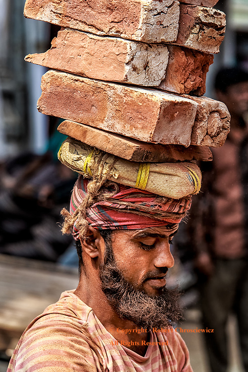 Brick Construction: A man exhibits exceptional balance, at a construction site, as he carries a precariously tall  stack of bricks atop his head, Mymensingh Bangladesh.