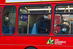 © Licensed to London News Pictures. 05/01/2021. London, UK. Commuters wearing protective face coverings travelling on a London bus as England begins its third national lockdown. Prime Minister Boris Johnson announced on Monday 4 January 2021 that England goes into third national lockdown until at least 22 February 2021, with households ordered to stay home and only go outside for the specific reasons. Photo credit: Dinendra Haria/LNP