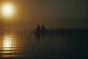Canoeing Sturgeon Lake in morning mist, Quetico Provincial Park, Ontario, Canada.