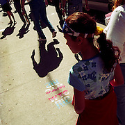 "Sprayed with aerosol and stencil on the pavement (sidewalk) in a Manhattan street near New York City's Armory are the words ""WTC RIP 9.11.2001""  As if in recognition of the attacks on the World Trade Center that occured four days previously, pedestrians pass-by leaving dark, haunted shadows on the pavement as if suffering the horrors of what many witnessed on September 11th. A young girl is about to walk over the stencil and we see her US stars and stripes bandana wrapped around her head looking like the tv super-hero Wonder Woman. ."