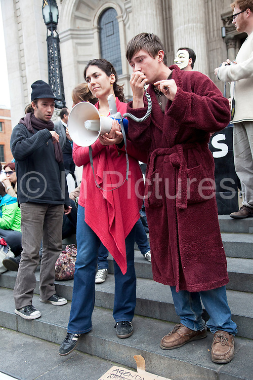 """People gathered listening to speakers, this one wearing a dressing gown. Occupy London protest at St Pauls, October 16th 2011. Protest spreads from the US with this demonstrations in London and other cities worldwide. The 'Occupy' movement is spreading via social media. After four weeks of focus on the Wall Street protest, the campaign against the global banking industry started in the UK this weekend, with the biggest event aiming to """"occupy"""" the London Stock Exchange. The protests have been organised on social media pages that between them have picked up more than 15,000 followers. Campaigners gathered outside  at midday before marching the short distance to Paternoster Square, home of the Stock Exchange and other banks.It is one of a series of events planned around the UK as part of a global day of action, with 800-plus protests promised so far worldwide.Paternoster Square is a private development, giving police more powers to not allow protesters or activists inside."""