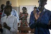 Aneno Margaret, center, claps in one hand during a mass in a catholic church in Gulu. She was abducted at the age of 11 in Acholi-bur village and was assigned to a commander two years later who had 13 wives. She also started a military training at that time and spent eight years as a soldier. She gave birth to two daughters in the bush. When she was 19 years old, a mortar attack at the frontline hit her arm and the chest, resulting in the amputation of one arm.