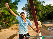 10 MAY 2016 - TA TUM, SURIN, THAILAND:     A man signals that his water tank is full to an attendant running a pump at the artesian well in Ta Tum, Surin, Thailand. The well is the most important source of drinking water for thousands of people in the communities surrounding it.  In the past many of the people had domestic water piped to their homes or from wells in their villages but those water sources have dried up because of the drought in Thailand. Thailand is in the midst of its worst drought in more than 50 years. The government has asked farmers to delay planting their rice until the rains start, which is expected to be in June. The drought is expected to cut Thai rice production and limit exports of Thai rice. The drought, caused by a very strong El Nino weather pattern is cutting production in the world's top three rice exporting countries:  India, Thailand and Vietnam. Rice prices in markets in Thailand and neighboring Cambodia are starting to creep up.     PHOTO BY JACK KURTZ