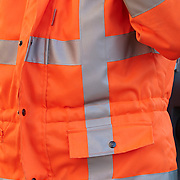 waist of a safety worker in an orange and silver striped jacket