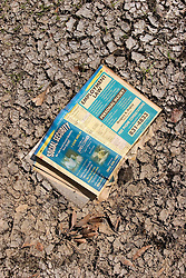 01 October, 05.  New Orleans, Louisiana. Lower 9th ward. Hurricane Katrina aftermath. <br /> The remnants of the lives of ordinary folks, now covered in mud as the flood waters recede.  A phone book lies open in the mud revealing the pages for Social Security and employment law.<br /> Photo; ©Charlie Varley/varleypix.com