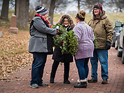 14 DECEMBER 2019 - DES MOINES, IOWA: Volunteers with Christmas wreaths walk through Woodland Cemetery looking for veterans' graves. Volunteers working with Wreaths Across America placed Christmas wreaths on the headstones of more than 600 US military veterans in Woodland Cemetery in Des Moines. The cemetery, one of the first in Des Moines, has the graves of veterans going back to the War of 1812.      PHOTO BY JACK KURTZ