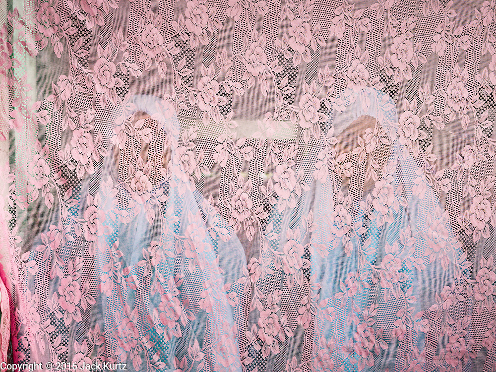 06 JULY 2016 - BANGKOK, THAILAND: Women participate in Eid services behind a privacy screen at Bang Luang Mosque in the Thonburi section of Bangkok. Eid al-Fitr is also called Feast of Breaking the Fast, the Sugar Feast, Bayram (Bajram), the Sweet Festival or Hari Raya Puasa and the Lesser Eid. It is an important Muslim religious holiday that marks the end of Ramadan, the Islamic holy month of fasting. Muslims are not allowed to fast on Eid. The holiday celebrates the conclusion of the 29 or 30 days of dawn-to-sunset fasting Muslims do during the month of Ramadan. Islam is the second largest religion in Thailand. Government sources say about 5% of Thais are Muslim, many in the Muslim community say the number is closer to 10%.        PHOTO BY JACK KURTZ