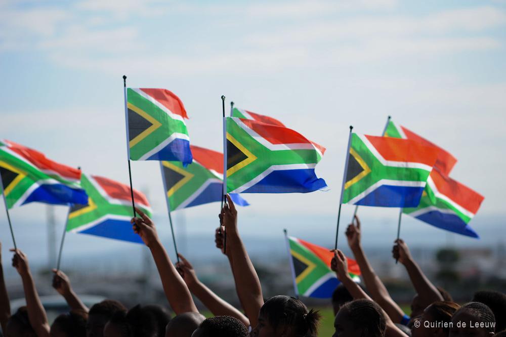 Scholieren houden vlaggen ophoog tijdens de vieren van Freedom Day in Zuid Afrika