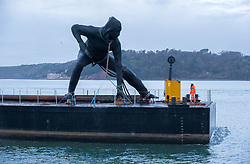 "© Licensed to London News Pictures. 18/03/2019. Plymouth, Devon, UK. ""Messenger"", the largest bronze sculpture ever to be cast in the UK, is transported by barge across Plymouth Sound before being installed at the Theatre Royal in Plymouth City Centre. Weighing in at nine and a half tonnes with a height of seven metres (23ft) and nine metres (30ft) wide, with a volume of 25.6 metres cubed, ""Messenger"" will be the size of two double decker buses and is the largest lost-wax cast bronze sculpture ever to be cast in the UK, a painstaking process that has taken over two years. ""Messenger"" is the work of the acclaimed sculptor Joseph Hillier and has been created using 3D scans from the body of a young actor in mid-performance in Theatre Royal Plymouth and Frantic Assembly's production of Othello in 2014. A monument to the physical expression of theatre, ""Messenger"" is a movement suspended in time that embodies the energy and creativity at the heart of the Theatre Royal and cultural life in Plymouth and aims to celebrate creativity as a dynamic catalyst for change. Plymouth is undergoing massive regeneration and the installation of the sculpture is is a prelude to the Mayflower 2020 celebrations. Messenger was cast at the Castle Fine Arts Foundry in the Welsh village of Llanrhaeadr-Ym-Mochnant, using the ancient technique of lost wax casting. Made from over 200 bronze panels, each section of the sculpture was cast individually before being welded together by over 30 master craftsmen at the foundry. Photo credit: Simon Chapman/LNP"