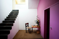 A telephone table next to a stair case on the ground level of the Casa Luis Barragan.