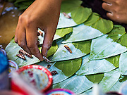 27 OCTOBER 2015 - YANGON, MYANMAR: A betel nut vendor prepares betel in the market at Aungmingalar Jetty in Yangon. The market is home to one of the largest fish markets in Yangon and a meat and produce market. Betel is a mild stimulant chewed by millions of Burmese.    PHOTO BY JACK KURTZ