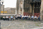 Local people sitting in front of the Chiesa Madre, at Ferla, Province of Siracusa, Sicily, Italy, during the hot noon hours, July 2006