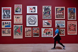 "© Licensed to London News Pictures. 07/11/2017. London, UK.  A student from Thomas Tallis School, Kidbrooke, south London, walks in front of Soviet political propaganda posters during their visit to the preview of ""Red Star Over Russia: A Revolution in Visual Culture 1905-55"" at Tate Modern.  The exhibition marks the centenary of the October Revolution and presents the visual history of Russia and the Soviet Union with works drawn from the late graphic designer David King. Photo credit: Stephen Chung/LNP"