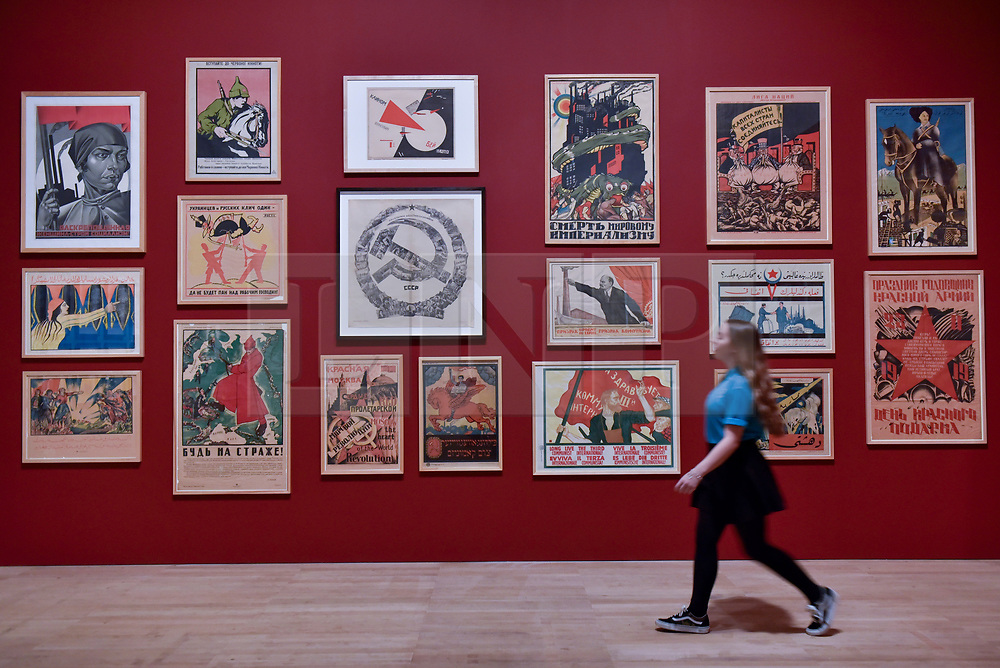 """© Licensed to London News Pictures. 07/11/2017. London, UK.  A student from Thomas Tallis School, Kidbrooke, south London, walks in front of Soviet political propaganda posters during their visit to the preview of """"Red Star Over Russia: A Revolution in Visual Culture 1905-55"""" at Tate Modern.  The exhibition marks the centenary of the October Revolution and presents the visual history of Russia and the Soviet Union with works drawn from the late graphic designer David King. Photo credit: Stephen Chung/LNP"""