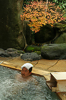 """Yajikitanoyu Onsen, Hakone - A man relaxing at an open air hot spring called a """"rotemburo"""" in Japan.  Bathing in a natural atmosphere, among the trees and under open skies, is a favorite with Japanese."""